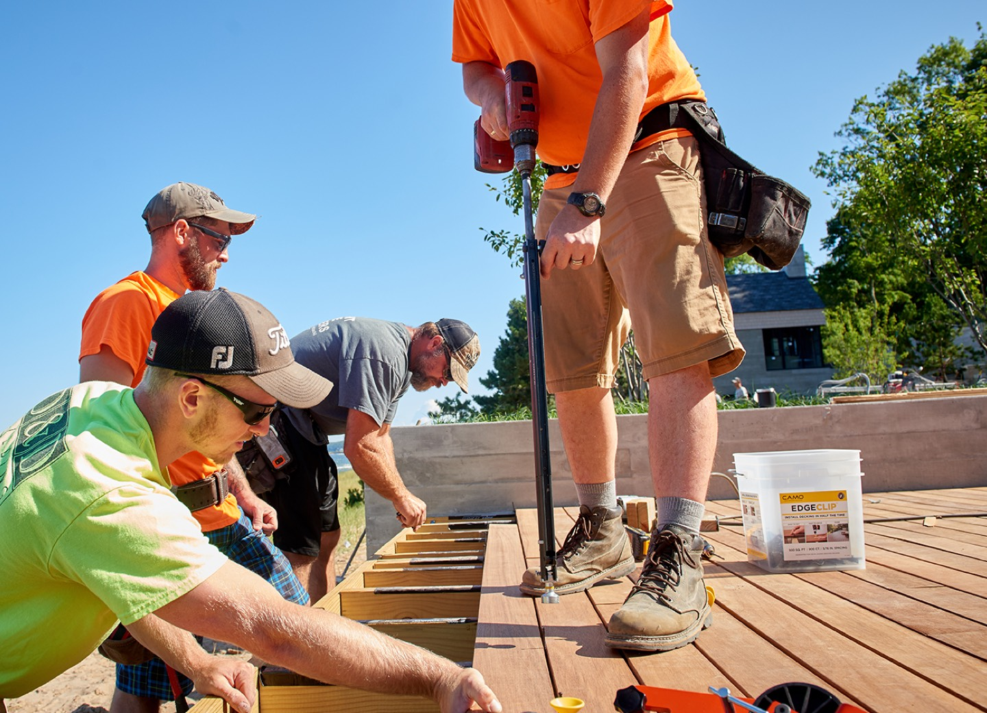 Crew installing deck boards with CAMO clips and DRIVE